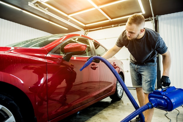 Der servicemitarbeiter trocknet das auto nach dem waschen automatisch.