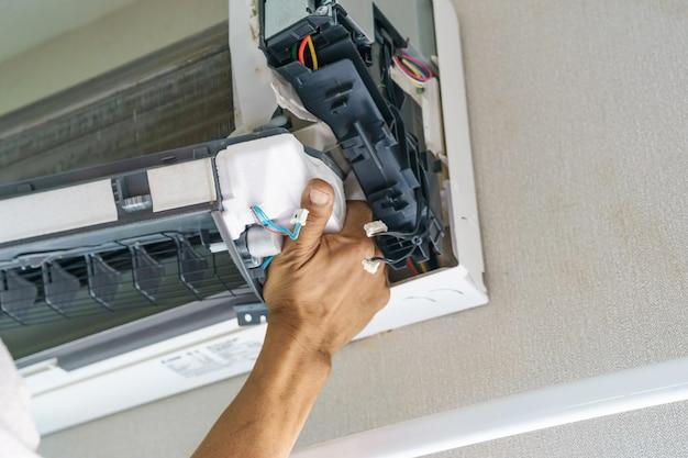 Der servicetechniker reinigt, repariert und wartet die klimaanlage