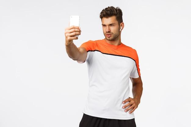 Der sexy junge männliche gefäßathlet, der selfie in der turnhalle nimmt, tragen activewear