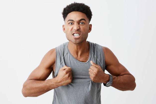 Der siegergeist ist stark. nahaufnahmeporträt des professionellen dunkelhäutigen kämpfers mit afro-frisur, die bereit ist, sein hemd zu werfen, um seinen gegner zu erschrecken. sport- und lifestyle-konzept
