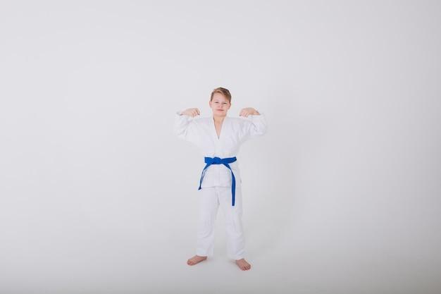 Der siegreiche junge in einem weißen kimono mit einem blauen gürtel an einer weißen wand