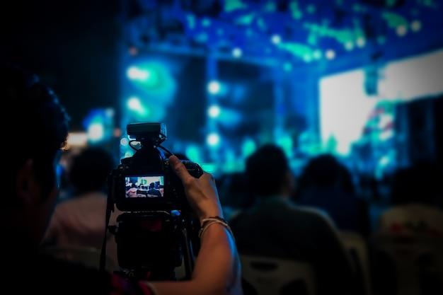 Der silhouette-videograf war für ein verschwommenes countdown-konzert mit bokeh in bangkok, thailand, aufgenommen worden.