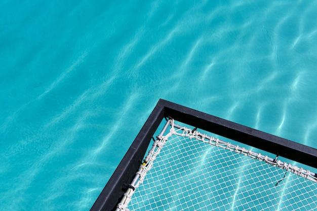 Der sitz aus mesh ragt am swimmingpool heraus