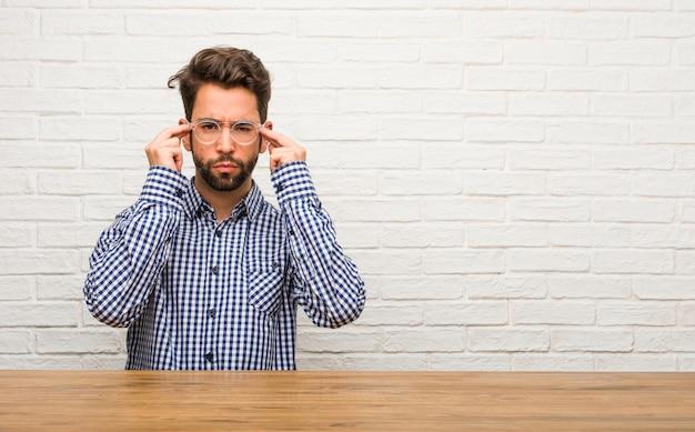 Der sitzende mann des jungen kaukasischen mannes, der eine konzentrationsgeste, geradeaus schauend gebildet wird, fokussierte auf ein ziel
