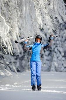 Der skifahrer, der sonnigen tag gegen schnee genießend steht, bedeckte bäume auf dem hintergrund