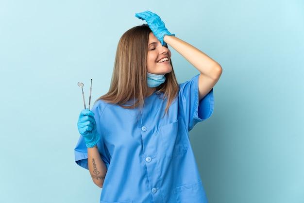 Der slowakische zahnarzt, der werkzeuge an der blauen wand hält, hat etwas erkannt und beabsichtigt, die lösung zu finden
