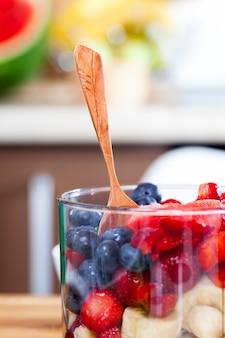 Der smoothie wird aus verschiedenen arten von beeren-smoothies hergestellt und besteht aus erdbeeren, blaubeeren und blaubeeren mit dem zusatz von bananen- und wassermelonenscheiben