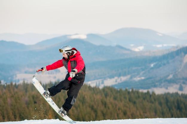 Der snowboardermann, der in schneepulver springt