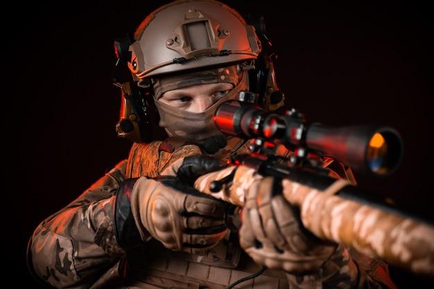 Der soldat der spezialeinheit im helm mit einem scharfschützengewehr