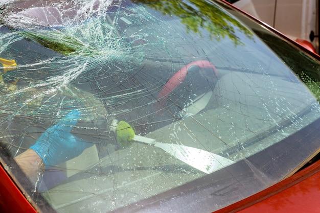 Der soldat, der windschutzscheibe auf einem auto entfernt, stürzte ein auto im dienst ab