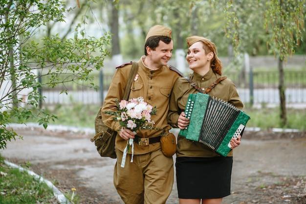 Der soldat geht die gasse entlang und umarmt eine militärfrau, die ein akkordeon spielt