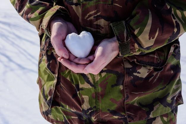 Der soldat nimmt das schneeherz in die hand.