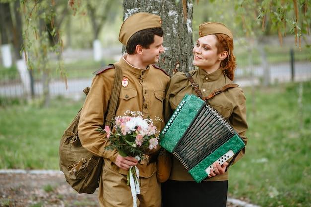 Der soldat umarmt eine militärfrau, die ein akkordeon spielt