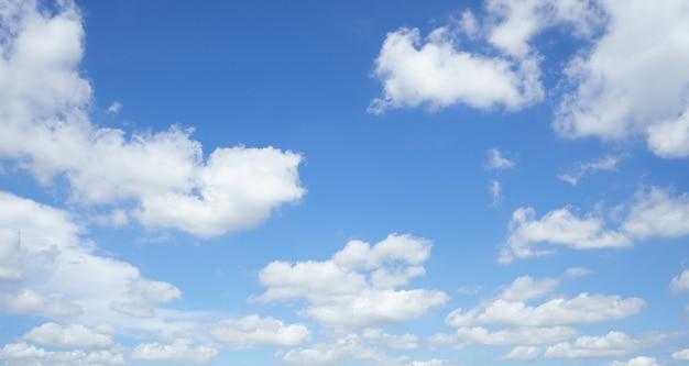 Der sommerhimmel ist hellblau. es schweben wolken durch. fühlen sie sich beim schauen entspannt.