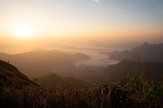 Der sonnenaufgang am berg mit nebel und wolken bedeckt ihn.