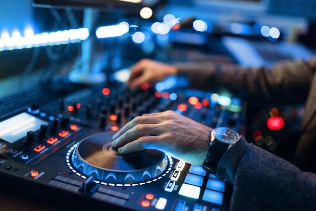 Der sound operator übergibt die fernbedienung im aufnahmestudio. musiker am mixer, professionelles audio-mixing