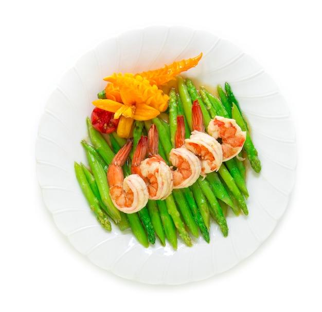 Der spargelaufruhr, der mit garnele gebraten wird, verzieren draufsicht der gelben paprika- und tomate geschnitzten art