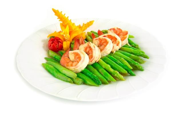 Der spargelaufruhr, der mit garnele gebraten wird, verzieren seitenansicht des gelben paprikas und der tomate geschnitzten art