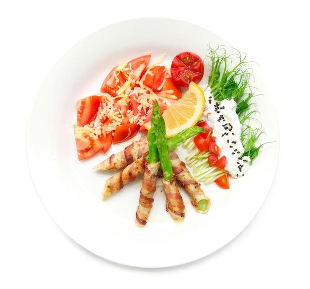 Der speck, der den spargel eingewickelt wurde, der mit erbsensprösslingsrollensalat auf oberstem griechischem joghurt gegrillt wurde, besprühen schwarzen sasemi und tomatensalat auf oberstem cheddarkäse, verzieren mit draufsicht der zitrone und der geschnitzten tomatenart
