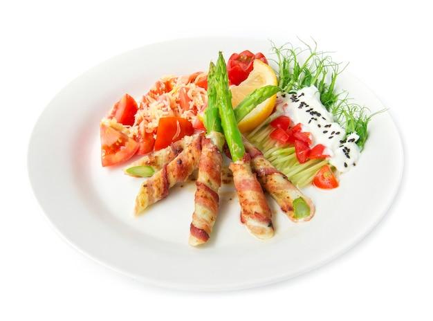 Der speck, der den spargel eingewickelt wurde, der mit erbsensprösslingsrollensalat auf oberstem griechischem joghurt gegrillt wurde, besprühen schwarzen sasemi und tomatensalat auf oberstem cheddarkäse, verzieren mit seitenansicht der zitrone und der geschnitzten tomatenart
