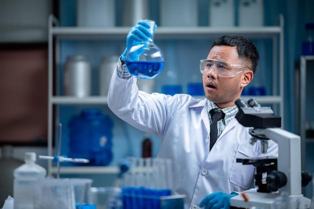 Der spezielle junge männliche wissenschaftler oder forscher, der die chemische lösung durch das reagenzglas für ein impfstoffexperiment sucht, das sich im modernen biologischen labor entwickelt