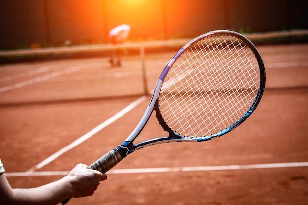 Der spieler, der einen tennisschläger hält. tennisplatz auf sand
