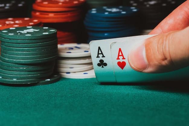 Der spieler zeigt ein paar asse beim poker vor dem hintergrund des spielens von chips auf dem grünen tisch