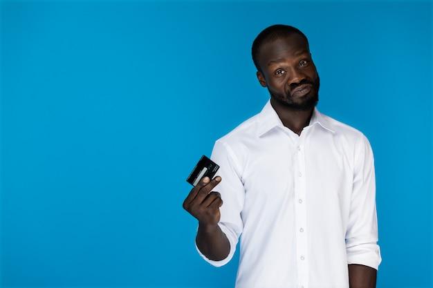 Der spielerische vorwärts schauende afroamerikanische mann im weißen hemd hält kreditkarte in der rechten hand