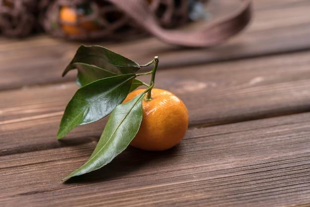 Der spin der mandarinen-nahaufnahme auf braunem hölzernem hintergrund. reife frucht.