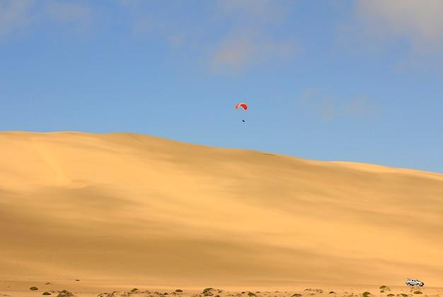 Der sport, von der sanddüne zu springen und im freien fall akrobatische manöver in der luft durchzuführen, bevor man mit dem fallschirm landet