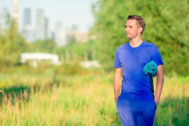 Der sportive junge mann, der sport tut, trainiert draußen im park