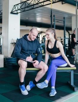 Der sportlehrer schreibt ein trainingsprogramm für eine sportliche blonde frau, die auf einer bank sitzt