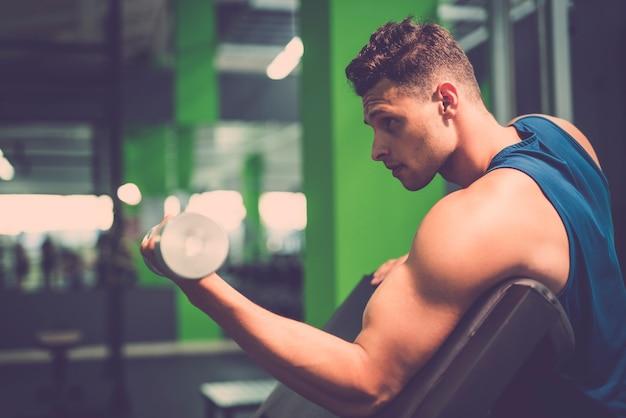 Der sportler beim bizepstraining mit einer hantel im fitnessstudio