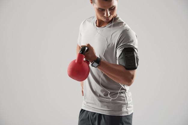 Der sportler, der bizeps tut, trainieren mit kettlebell