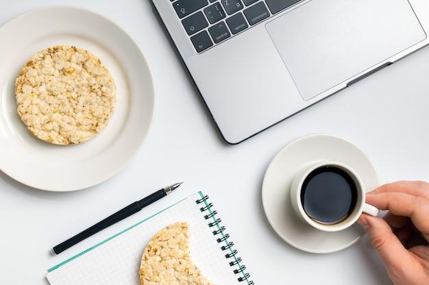 Der sportler, der knusperigen reis isst, rundet mit kaffee nahe dem laptop und dem notizbuch ab.
