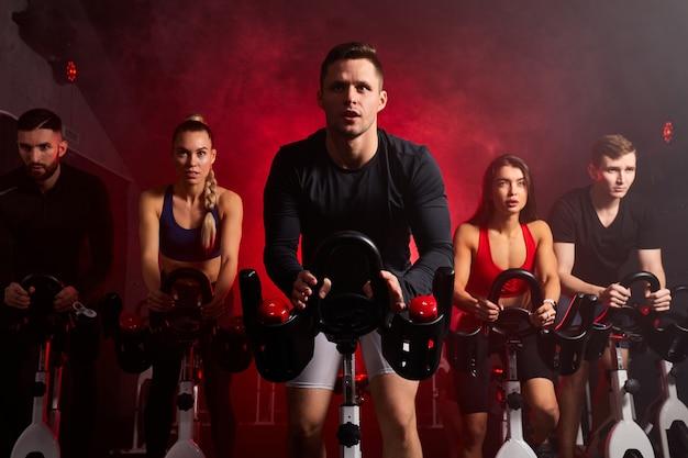Der sportler fährt fleißig ein heimtrainer im fitnessstudio und trainiert auf einem stationären fahrrad