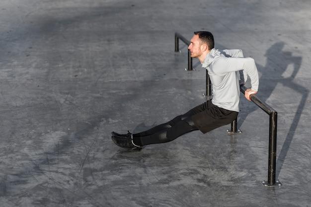 Der sportliche mann, der trizeps tut, trainiert draußen