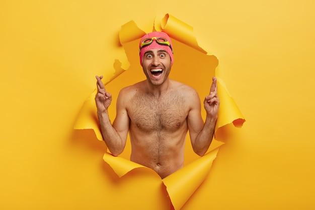 Der sportliche schwimmer ohne hemd trägt eine badekappe mit schutzbrille und drückt die daumen