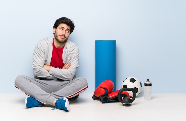 Der sportmann, der auf dem boden macht zweifel sitzt, gestikulieren beim anheben der schultern