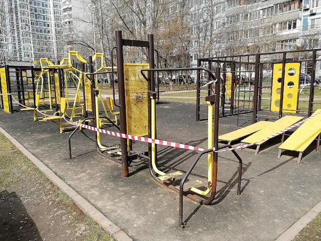 Der sportplatz an der straße ist gesperrt und mit klebeband eingezäunt. quarantänemaßnahmen zur verhinderung der ausbreitung des coronavirus. selbstisolation von menschen