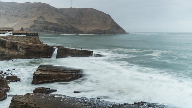 Der sprung des mönchs, berühmte klippe in chorrillos lima peru, gruppe riesige felsen in der küste, wellen schlagen die felsen rock
