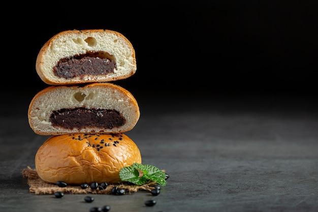 Der stapel gebackener schwarzer bohnenpastenbrötchen liegt auf einem dunklen boden