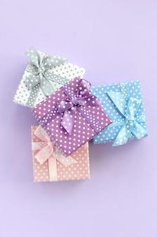 Der stapel von kleinen farbigen geschenkboxen mit bändern liegt auf veilchen