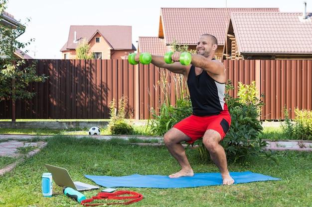 Der starke mann treibt sport im park. fröhlicher sportlicher mann mit schwarzem haar macht eine hocke mit hanteln und uhren im laptop und dreht blog im garten