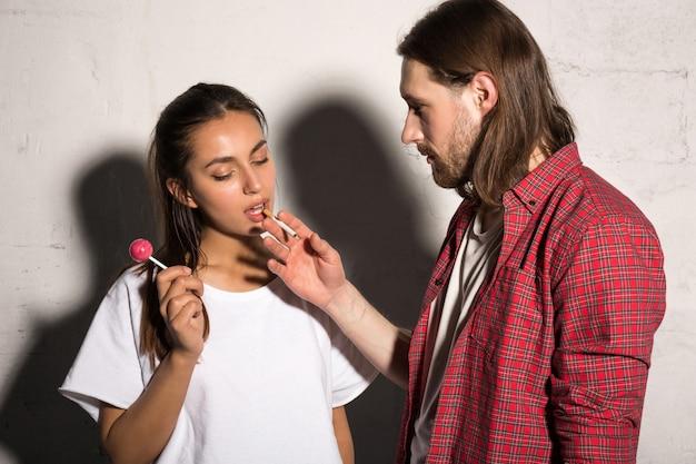 Der stehende mann gibt der freundin eine zigarette