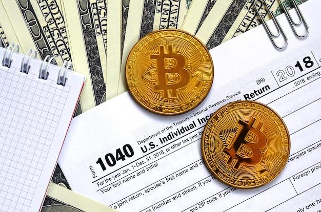 Der stift, bitcoins und dollarnoten liegen auf dem steuerformular
