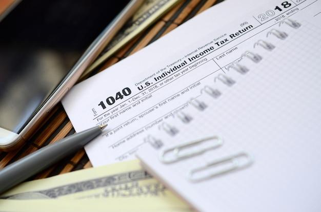 Der stift, das notizbuch, das smartphone und die dollarnoten liegen auf dem steuerformular 1040 us