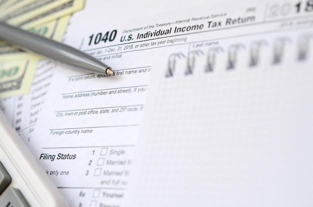Der stift, das notizbuch, der taschenrechner und die dollarnoten liegen auf dem steuerformular 1040 us-einkommensteuererklärung.