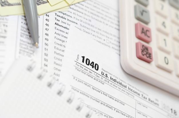 Der stift, das notizbuch, der taschenrechner und die dollarnoten liegen auf dem steuerformular 1040 us
