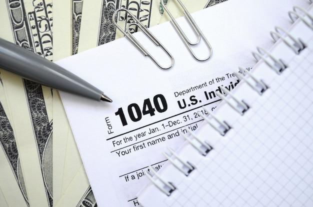 Der stift, das notizbuch und die dollarnoten liegen auf dem steuerformular 1040 us-einkommensteuererklärung. die zeit, um steuern zu zahlen